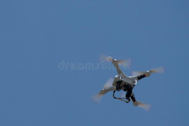 Remote control drone helicopter hovering in sky. Remote control drone helicopter hovering in the sky stock image