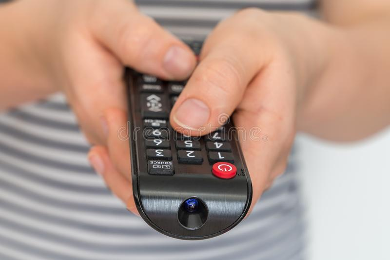 Remote control in female hands pointing to TV stock photo
