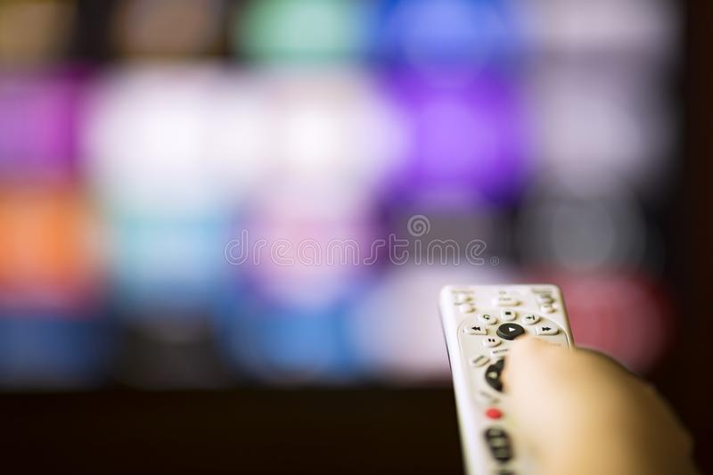 Remote control in hand in front of smart tv. Changing chanels with remote control in front of smart tv royalty free stock photography