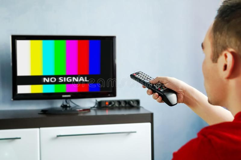 Remote control in hand in front of TV. Couch potato. No signal screen banner stock photo