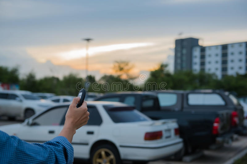 Remote control key Car in hand In the outdoor parking lot at evening. System automatic royalty free stock images