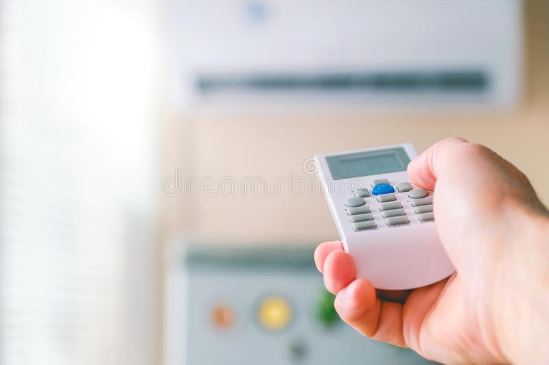 Remote control. Male hand with air conditioning remote control. The man switches the modes of conditioning. Regulates the cooling royalty free stock photos