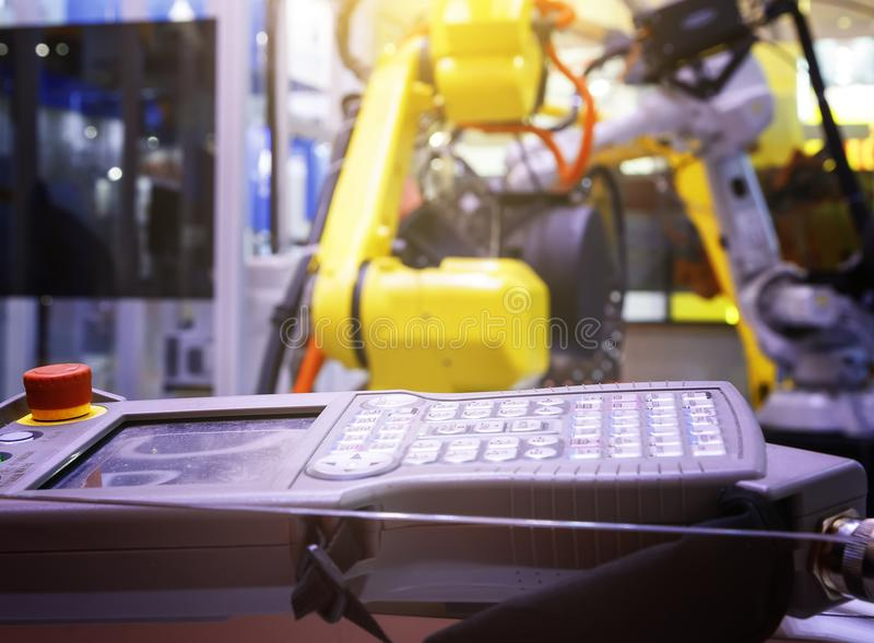 Remote control of a new and modern metal machines against the background of blurred yellow industrial robots royalty free stock photography