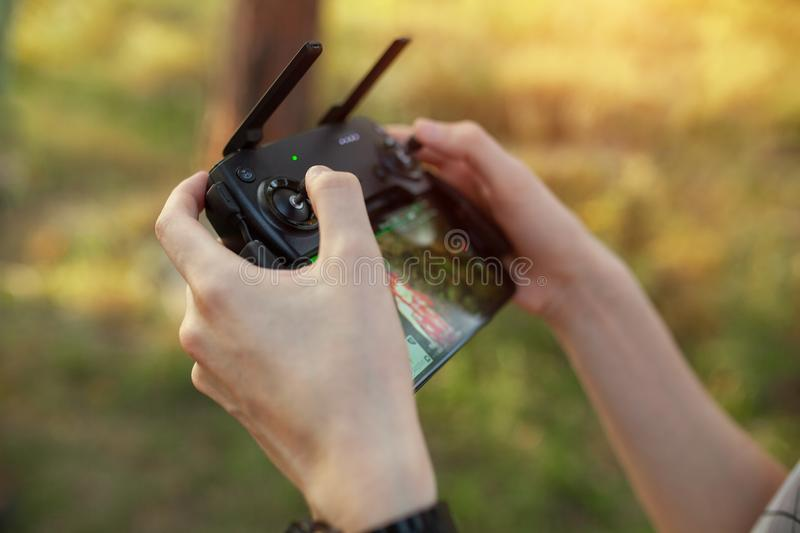 Remote control for quadrocopter, close-up. Transmitter for controlling moving device in male hands, blurred nature background. stock images