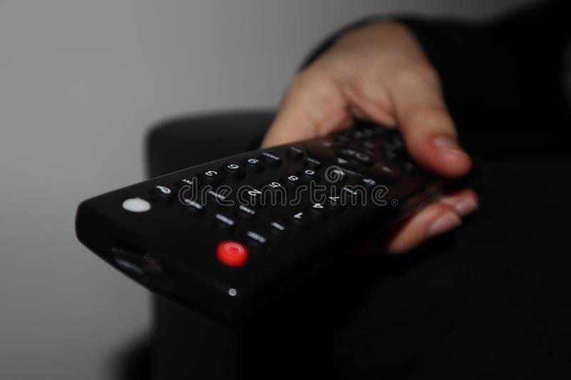 Remote control in woman hand stock image