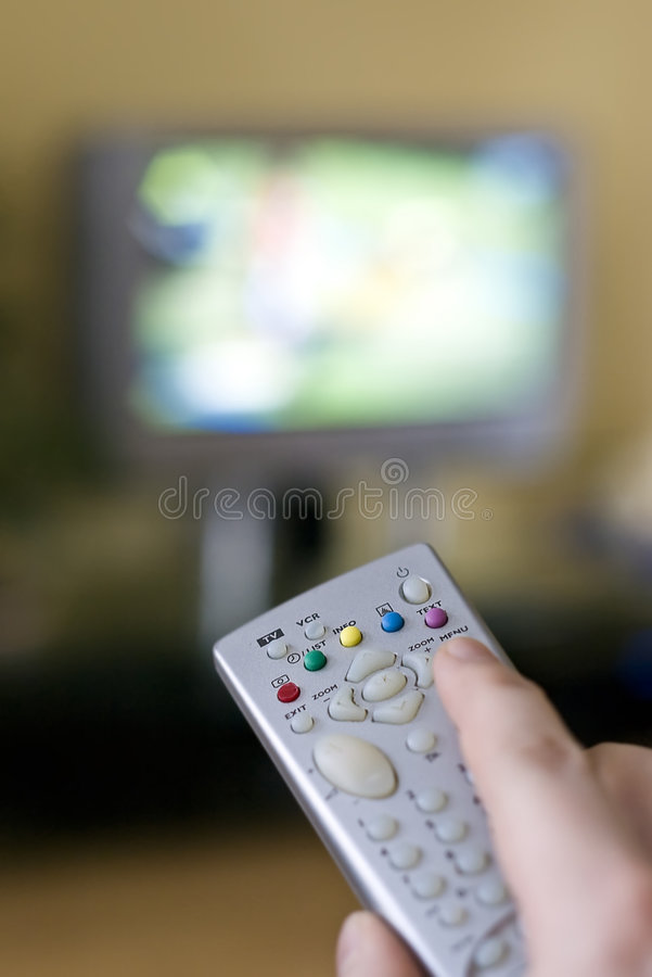 Remote controller. Hand on the TV remote controller changing television programme, the screen and its content blurred stock photos