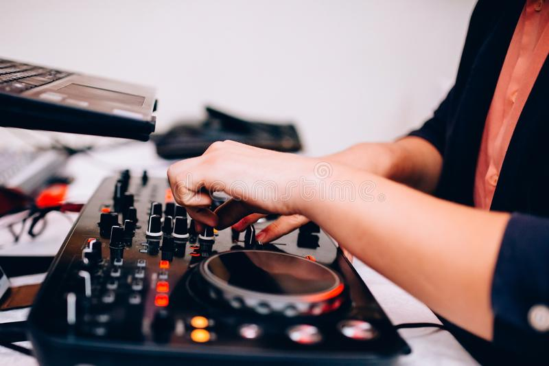 Close-up of musician`s hand on remote in nightclub royalty free stock photography