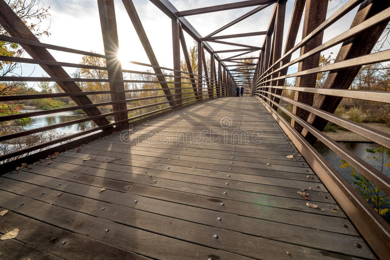 Remote foot bridge on Boise river with walkers. Walkers cross a foot bridge on the Boise River stock photos