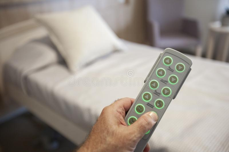 Adjustable hospital bed. A remote in hand controlling an adjustable hospital bed royalty free stock image