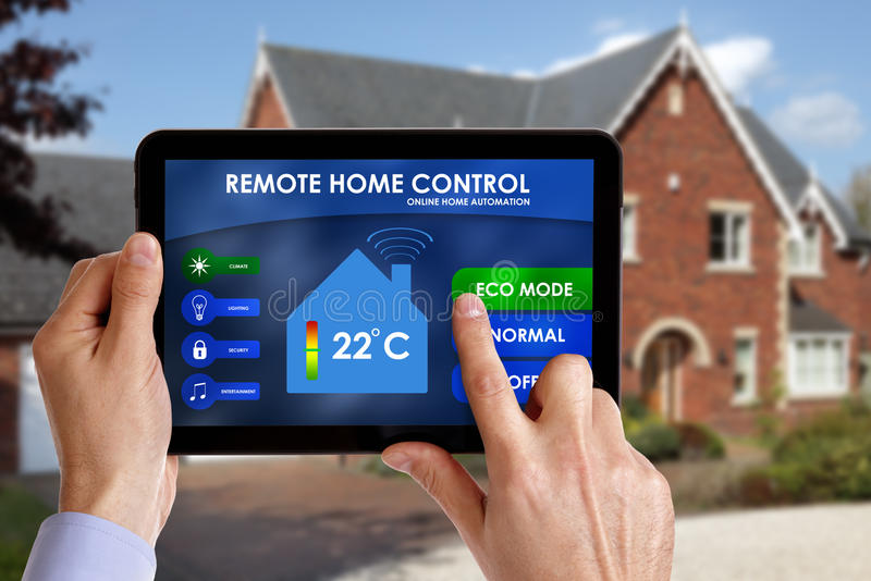 Remote home control. Holding a smart energy controller or remote home control online home automation system on a digital tablet. All screen graphics made up