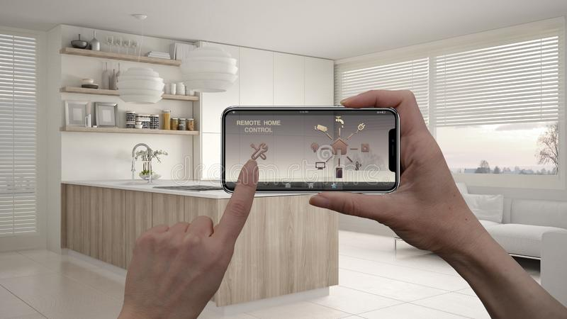 Remote home control system on a digital smart phone tablet. Device with app icons. Interior of modern kitchen with shelves and cab. Inets in the background royalty free stock images