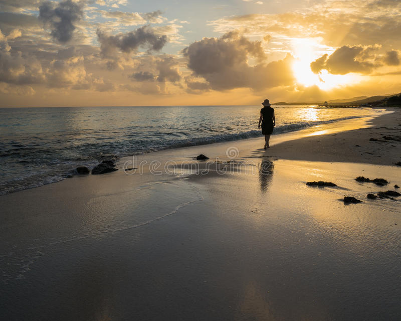 Remote Jamaican beach wth silhouetted woman walking stock photos