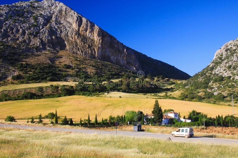 Remote rural valley with crop field and mountain face under blue sky - Sierra Nevada royalty free stock photography