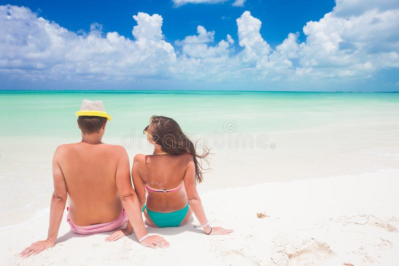 Back view of a man and woman couple sitting on a Jetty under a blue cloudy sky stock photos