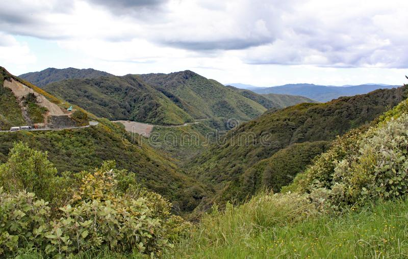 A remote valley in New Zealand. Trucks are on the road and construction vehicles are working stock image