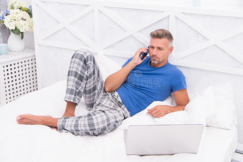 Remote work concept. Social networks. Online world. Man surfing internet work online. Digital marketing. Remote access. Mature man pajamas freelance worker royalty free stock photo