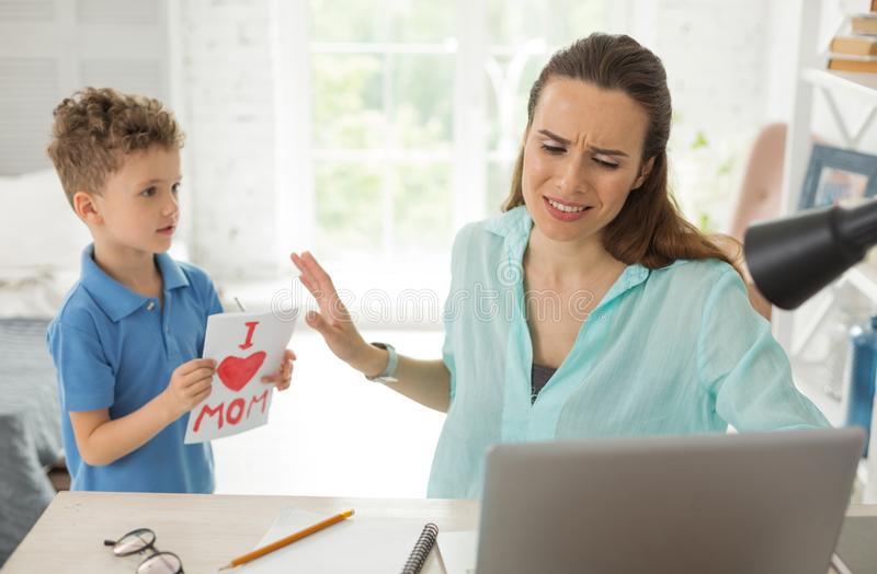 Remote worker feeling very busy while little son coming to her stock images
