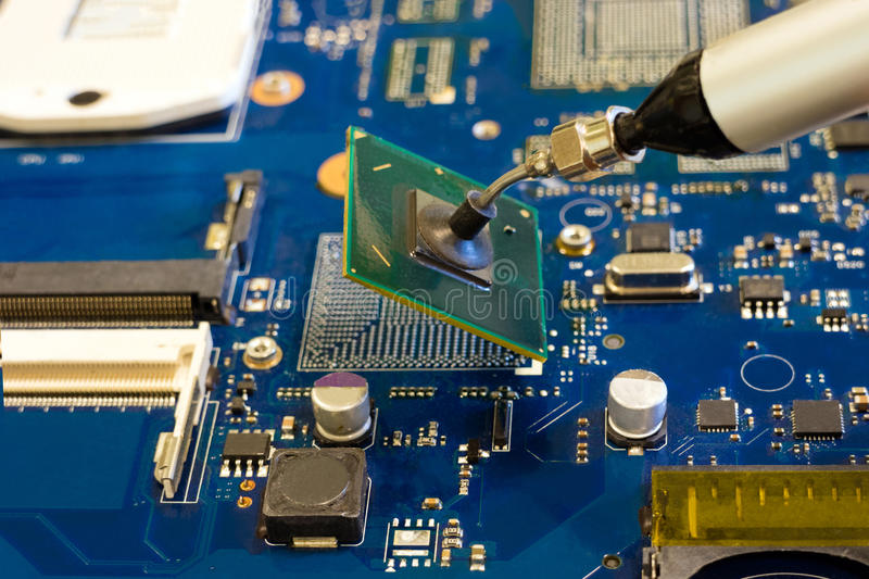 Removal of the chip by vacuum tweezers. Work on the disassembling of electronic components stock images