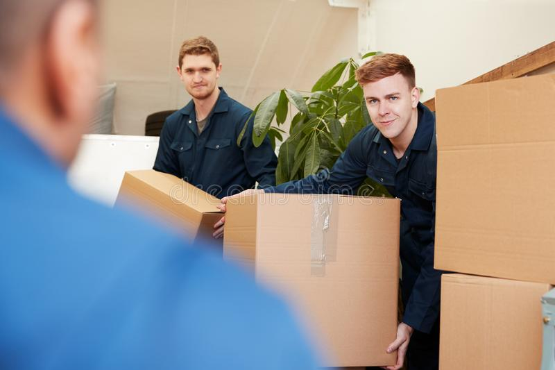 Removal Company Workers Unloading Furniture And Boxes From Truck Into New Home On Moving Day royalty free stock photos