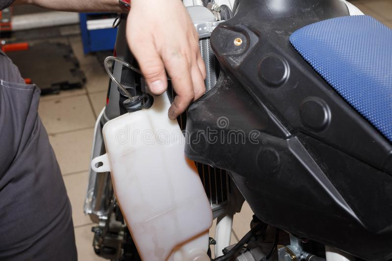 Removal, installation of a tank of the oil cooling system on a motorcycle. Troubleshooting a node stock photos