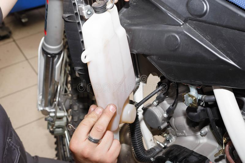 Removal, installation of a tank of the oil cooling system on a motorcycle. Troubleshooting a node royalty free stock image