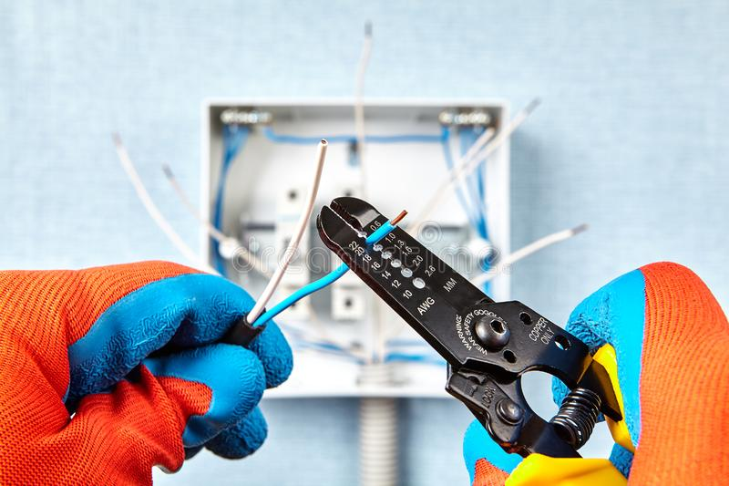 Remove insulation of electrical wire with stripper royalty free stock photo