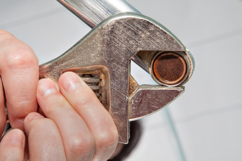 Remove old aerator from tap with an adjustable spanner, closeup. Remove the old aerator from the faucet with an adjustable wrench, close-up stock photography