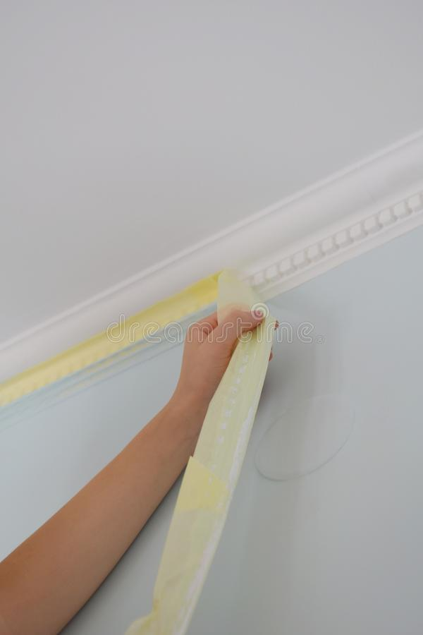 Remove paper masking tape from after painting. Removing masking tape from wall. royalty free stock photography