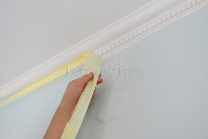 Remove paper masking tape from after painting. Removing masking tape from wall. Remove paper masking tape from after painting. Removing masking tape from wall royalty free stock photo