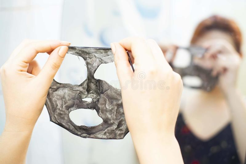 Cosmetic black mask. The removed layer of the black mask in woman hands. Summer day royalty free stock photography