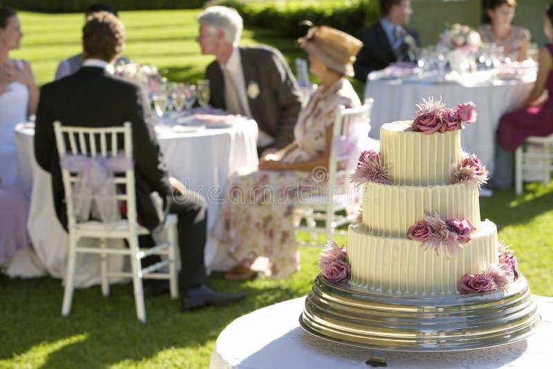 Removendo ervas daninhas do bolo com os convidados no fundo fotos de stock