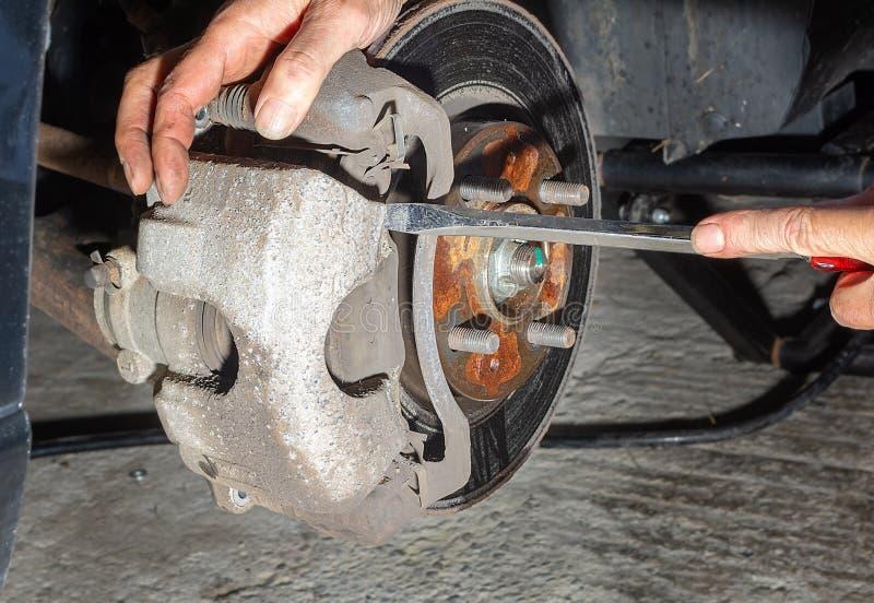 Removendo o compasso de calibre ao substituir freios do carro foto de stock