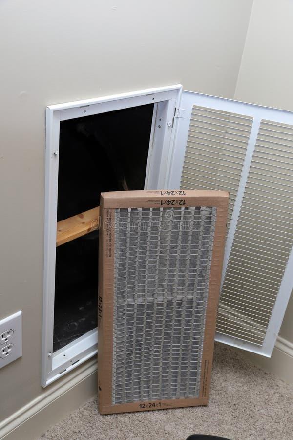 Removendo o filtro de ar sujo para o condicionador de ar da casa imagens de stock