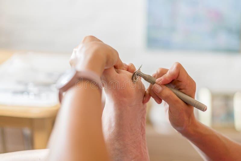 Remover δερμάτων Pedicure νεκρή rasp ποδιών γυναίκα στο σαλόνι καρφιών Αφαίρεση των δημητριακών στο πόδι με ένα ξυράφι στοκ εικόνα με δικαίωμα ελεύθερης χρήσης