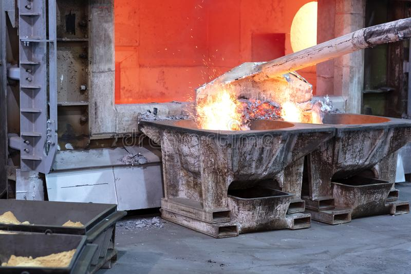 Removing aluminum dross. Skimming melted aluminum for removing the dross before casting. Aluminum foundry works showing an open furnace stock photo