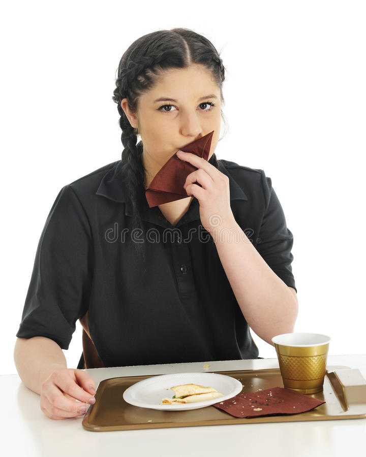 Removing the Crumbs. An attractive teen girl wiping the crumbs from her lips after enjoying a fast food breakfast. On a white background royalty free stock photo