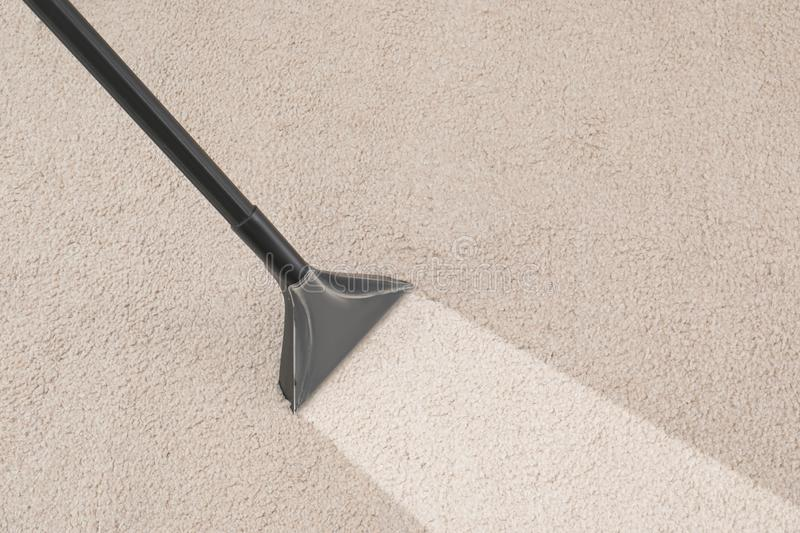 Removing dirt from carpet with vacuum cleaner stock photo
