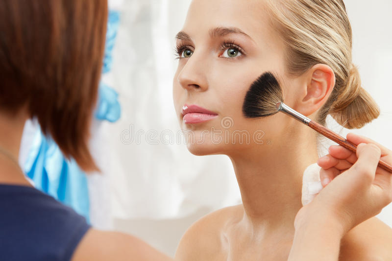 Removing excess of powder using fan brush stock photos