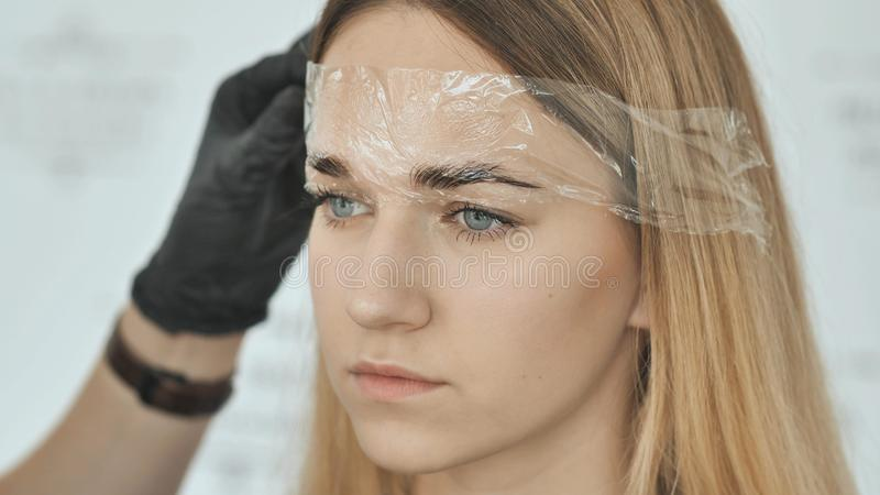 Removing the fixing film. Create permanent eyebrow makeup. royalty free stock photography