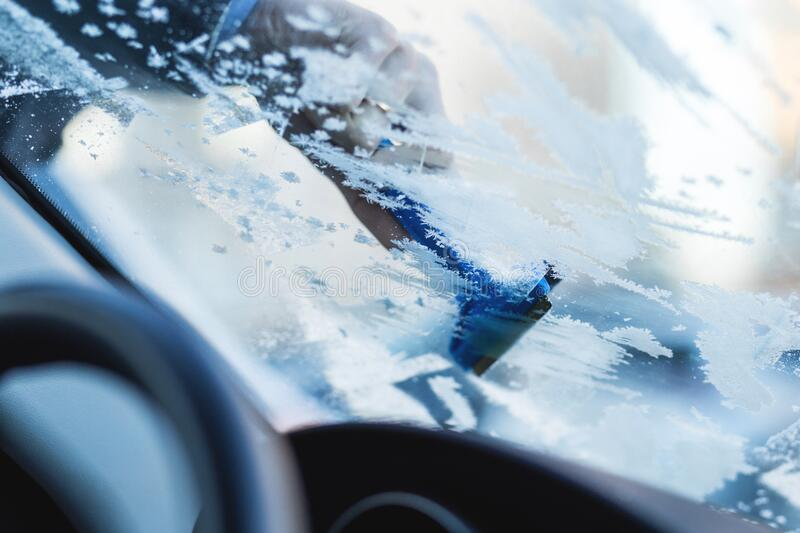 Removing frost from car windshield stock photography