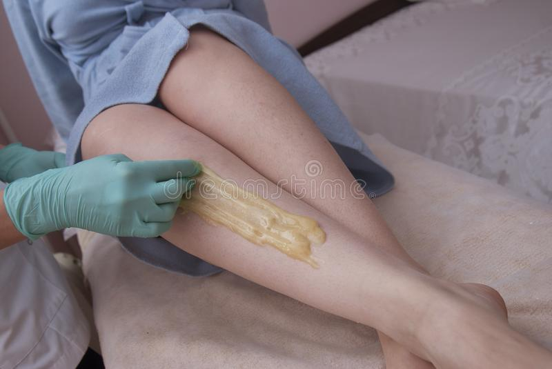 Removing Hair on Women& x27;s legs. Procedure sugaring in a beauty salon. Sugar depilation. Depilatory sugar paste. Removing Hair on Women& x27;s legs. Procedure stock photography