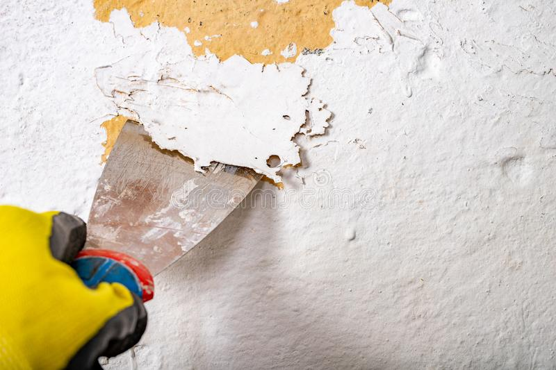 Removing old paint from the wall with a metal spatula. Small painting works at home stock photos