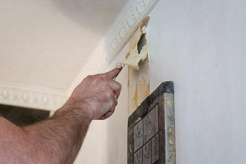 Removing the old wallpaper of the wall by using a steam device a. Nd filling knife stock photo