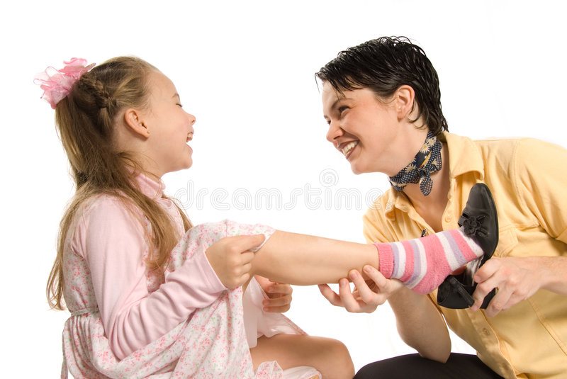 Removing shoe. Mom and daughter playing dress-up on white background royalty free stock photos