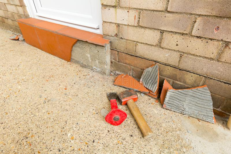 Removing Tiles. Removing terracotta tiles from a door step using a hammer and bolster stock photography