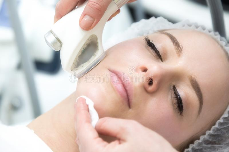 Removing wrinkles on the face and neck with massage. A beautiful blonde smooths wrinkles on the face and neck area with the help of massage in the beauty salon royalty free stock images