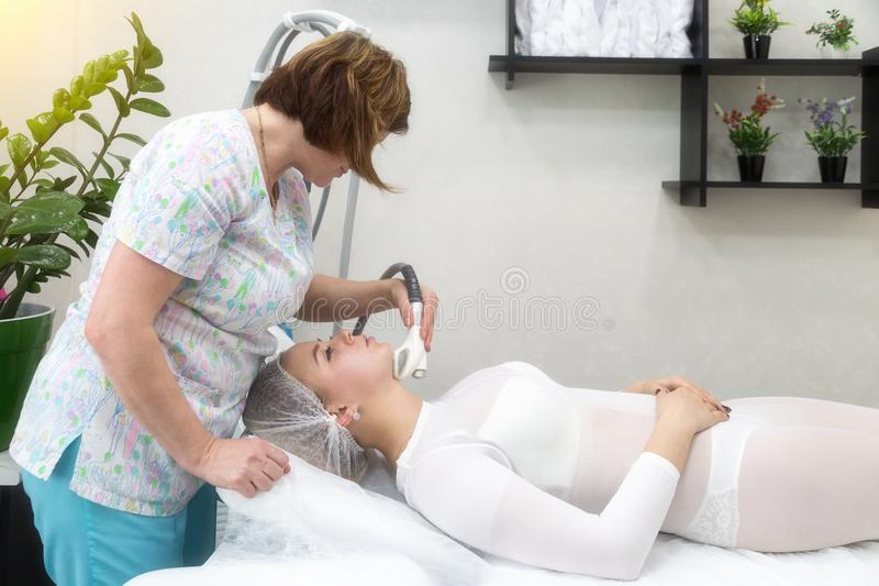 Removing wrinkles on the face and neck with massage. A beautiful blonde smooths wrinkles on the face and neck area with the help of massage in the beauty salon royalty free stock photos