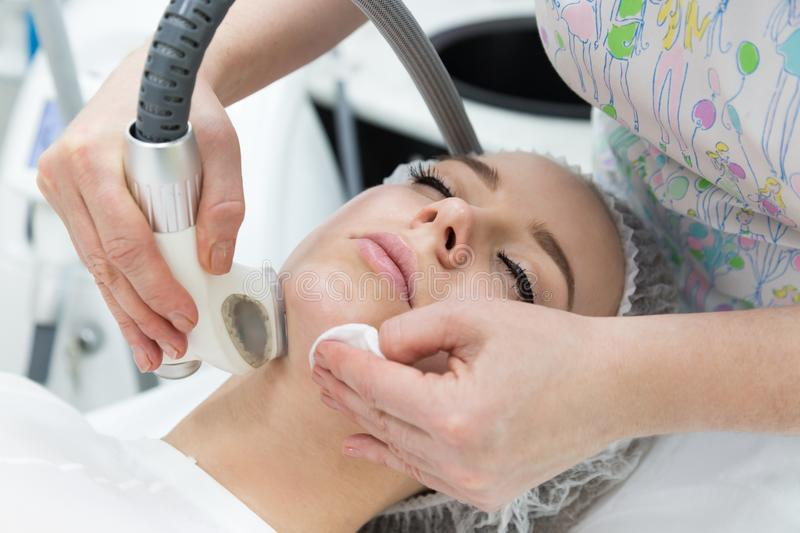 Removing wrinkles on the face and neck with massage. A beautiful blonde smooths wrinkles on the face and neck area with the help of LPG massage in the beauty royalty free stock images