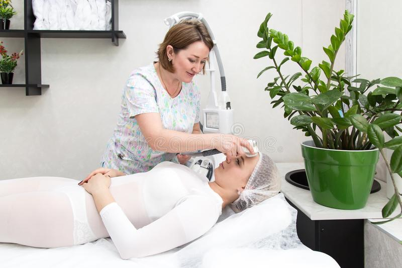 Removing wrinkles on the face and neck with massage. A beautiful blonde smooths wrinkles on the face and neck area with the help of LPG massage in the beauty stock photos