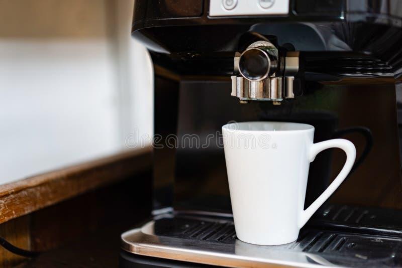 Remplaçant de tasse de café blanc sur la machine professionnelle de café prête à faire le café chaud frais photo stock